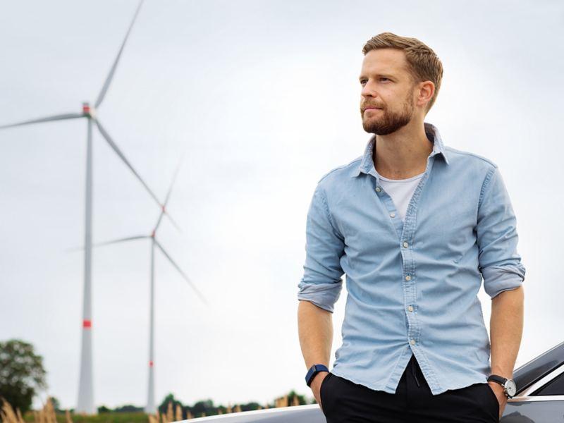 Ein Mann steht vor einem Windrad