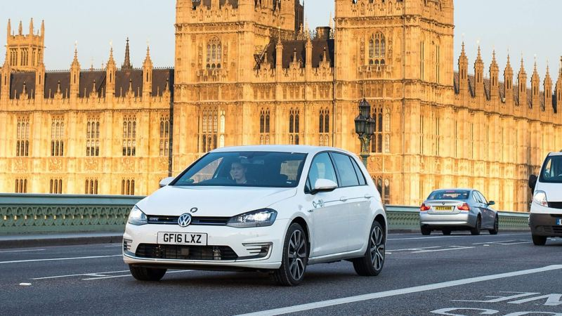 An e-Golf GTE driving across Westminster bridge in front of the Houses of Parliament