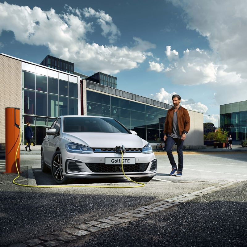 A man charging his white Volkswagen Golf GTE electric vehicle in front of a building