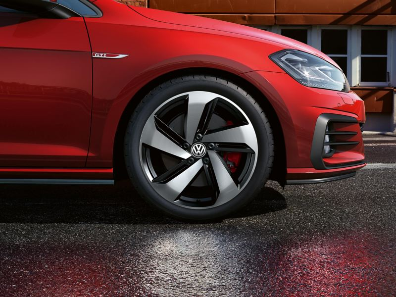 Front profile view of a red Volkswagen Golf GTI, main focus on the wheel,