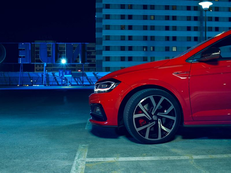 Profile view of a red Volkswagen Polo GTI, dipped halogen headlight with darkened city buildings at night.