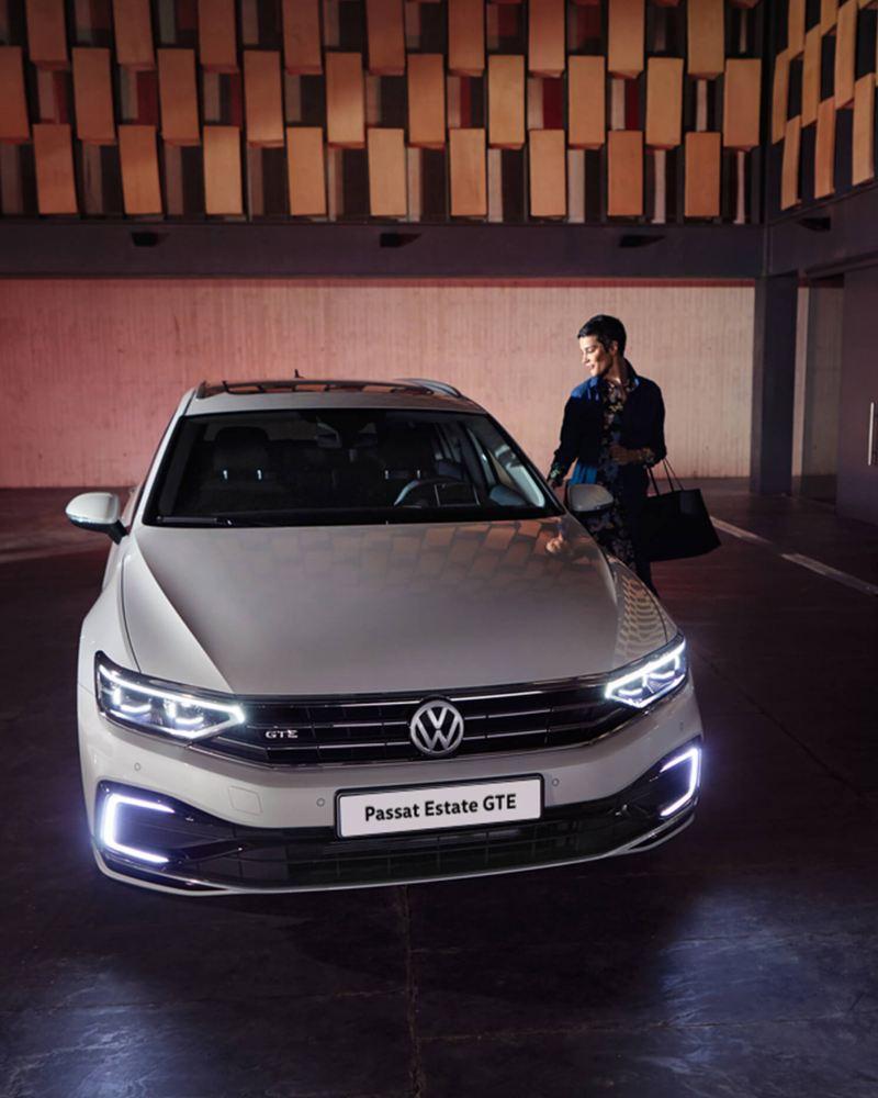 A man next to a while Volkswagen Passat GTE, in a darkened space, halogen headlights on.