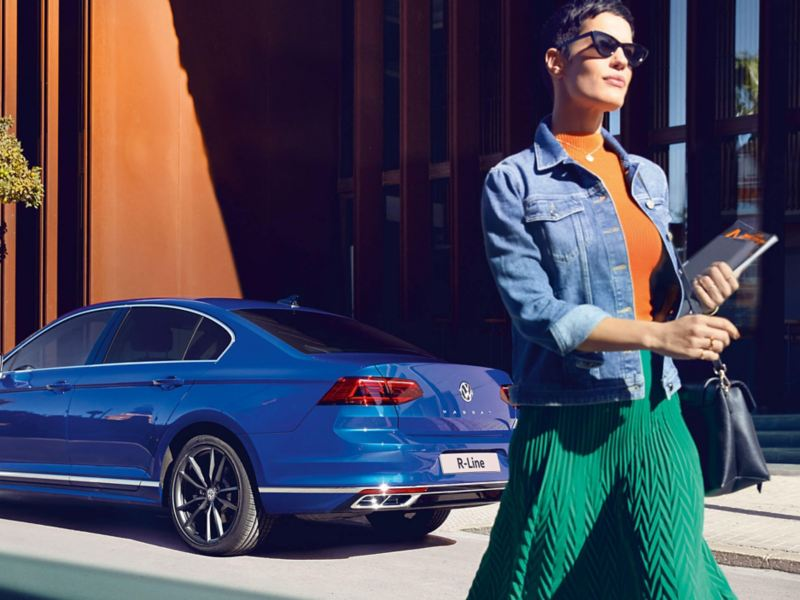 A lady walking past a blue Volkswagen Passat Saloon R-Line, rear profile shot.