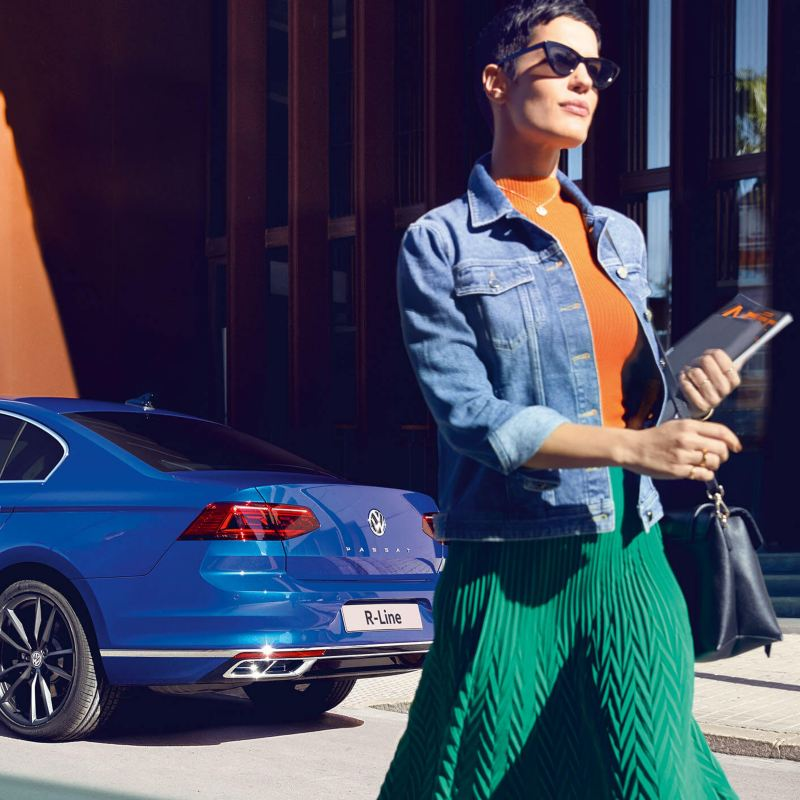 A blue Volkswagen Passat R-Line, outside a bustling city street with a lady walking by,