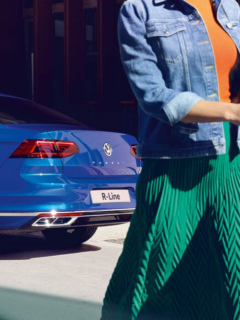 A lady walking past a blue Volkswagen Passat Saloon R-Line, rear profile shot.