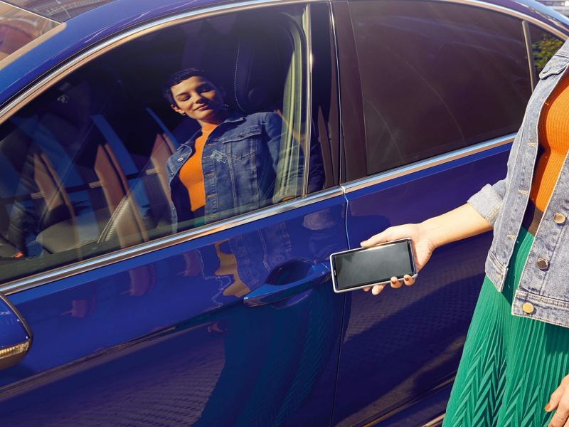 A lady holding her phone, indication the 'Proactive Passenger Protection System', next to a blue Volkswagen Passat.