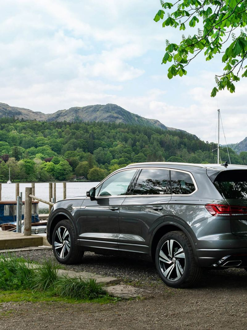 A silver Volkswagen Touareg parked near a lake