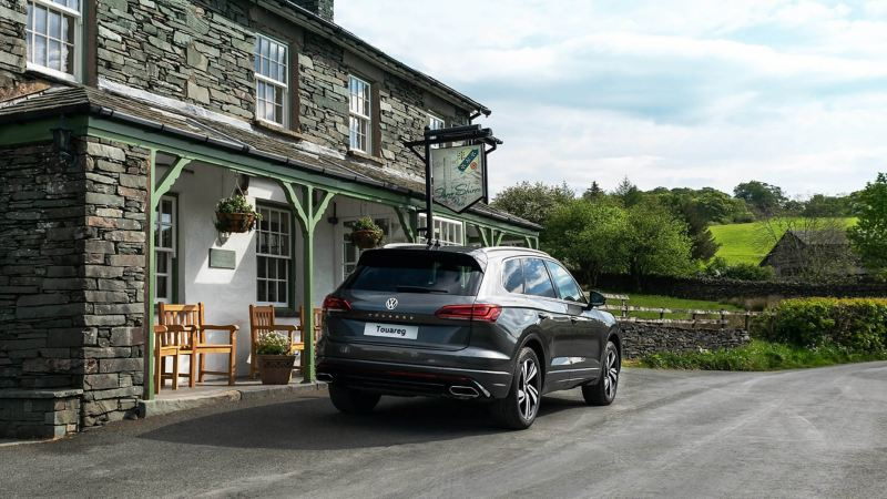 A silver Volkswagen Touareg parked near a cottage
