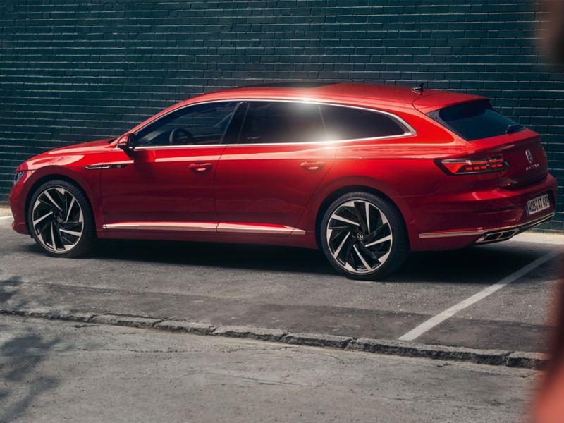 A red all new Arteon Shooting Brake parked in front of a building