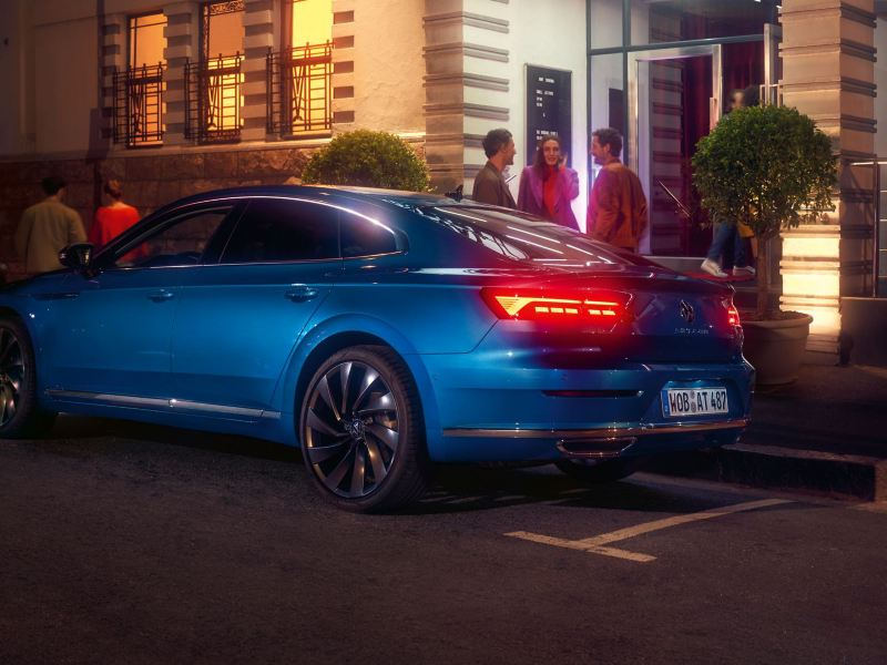 A blue New Arteon in a city street parking space.