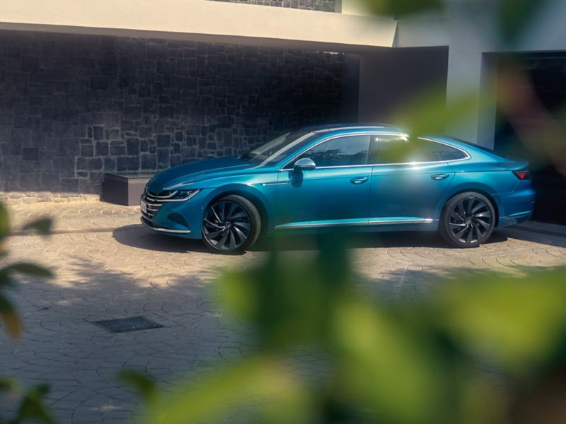 A blue new Arteon parked in front of a building