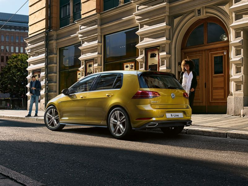 A yellow Volkswagen Golf R-Line, outside colonial city buildings.