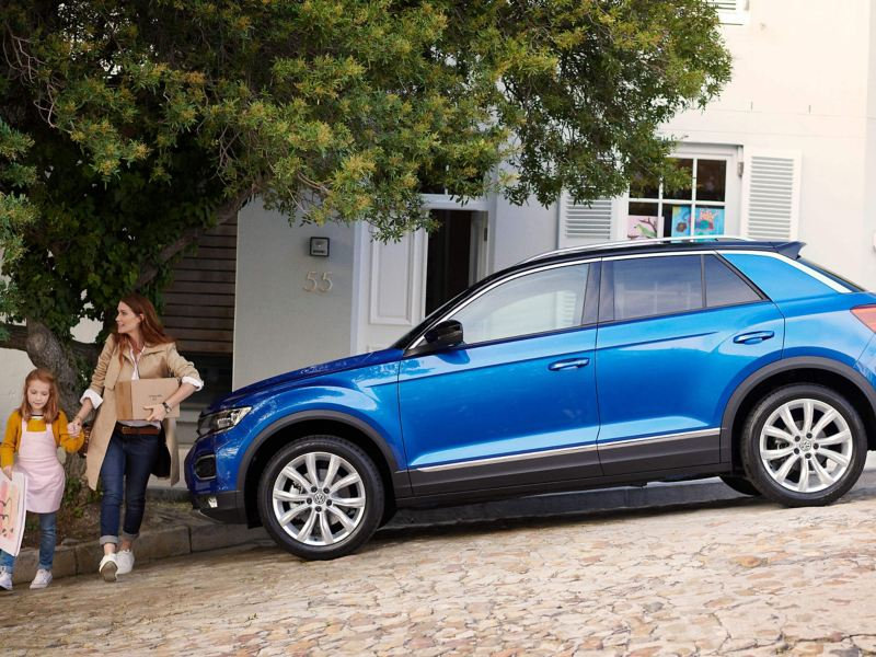 A profile view of a blue Volkswagen T-Roc parked on a steep street outside a family home, a mother and young girl crossing the road.
