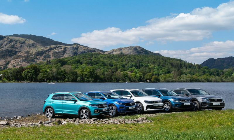 A Volkswagen T-Roc, T-Cross, Tiguan, Tiguan Allspace and Touareg parking in the mountains in front of a lake.