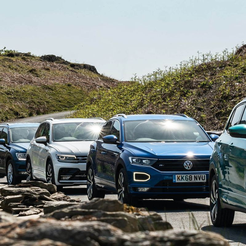 The Volkswagen SUV range, a T-Cross, a T-Roc, a Tiguan, a Tiguan Allspace, and a Touareg parking in the mountains