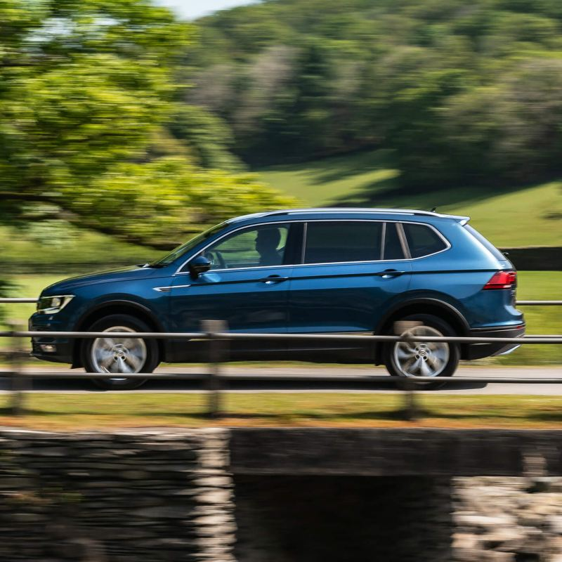 A Green Volkswagen Tiguan Allspace driving on a country road.