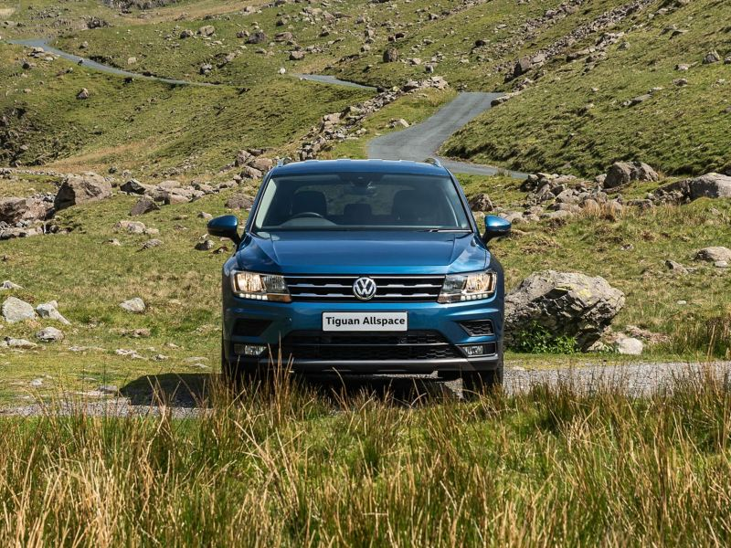 A green Tiguan Allspace in the countryside, parked a mountain road.