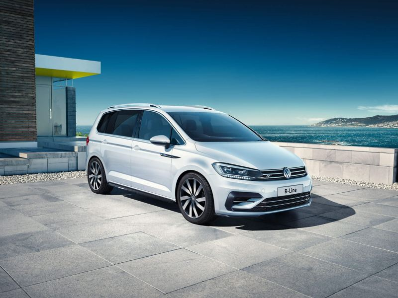 A white Volkswagen Touran outside a building with a bay and white cliffs in the background.