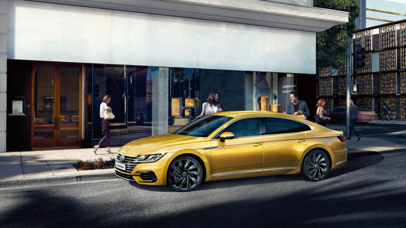 A yellow Volkswagen Arteon parked on the street in front of office buildings