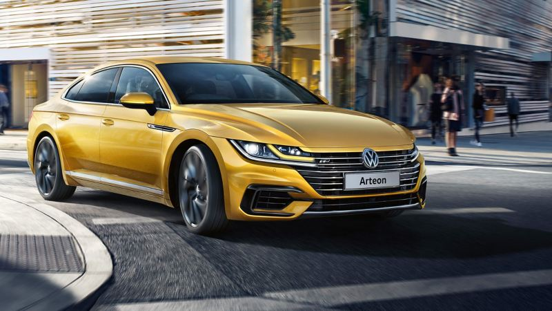 A yellow Volkswagen Arteon turning a corner of a city street, with pedestrians crossing the road in the background.