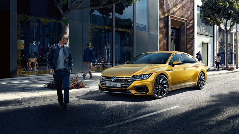 A yellow Volkswagen Arteon parked on the street in front of office buildings, as pedestrians pass-by