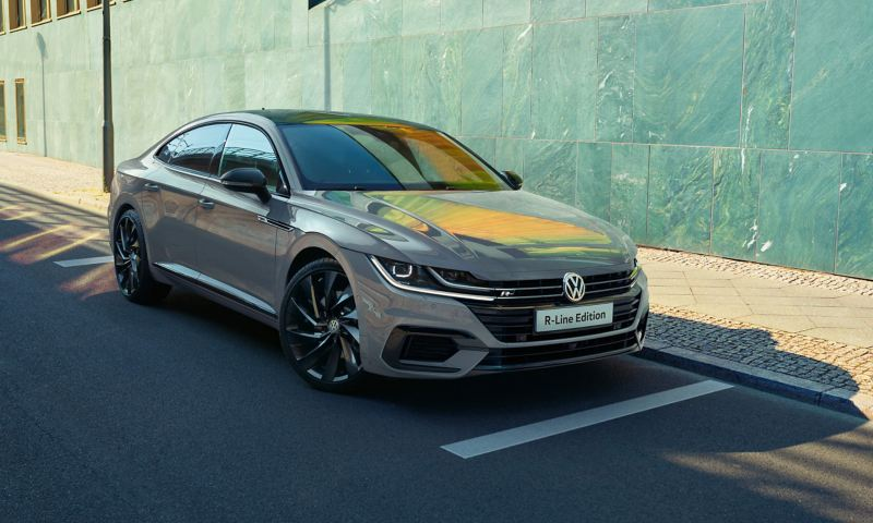A grey Arteon R-Line Edition parked in front of a wall with tiles