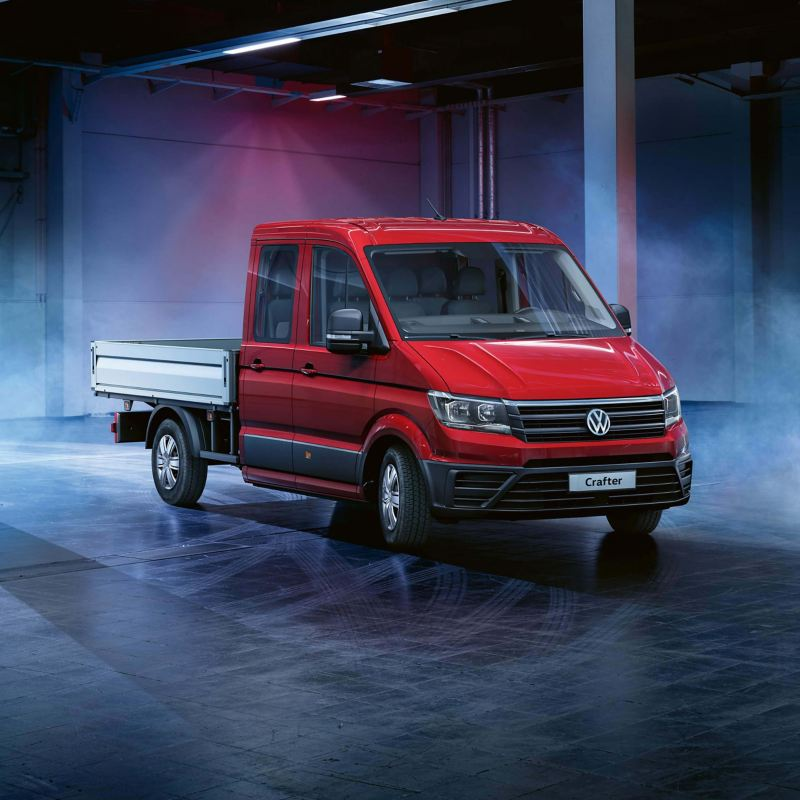 A red Volkswagen crafter parked in a warehouse.