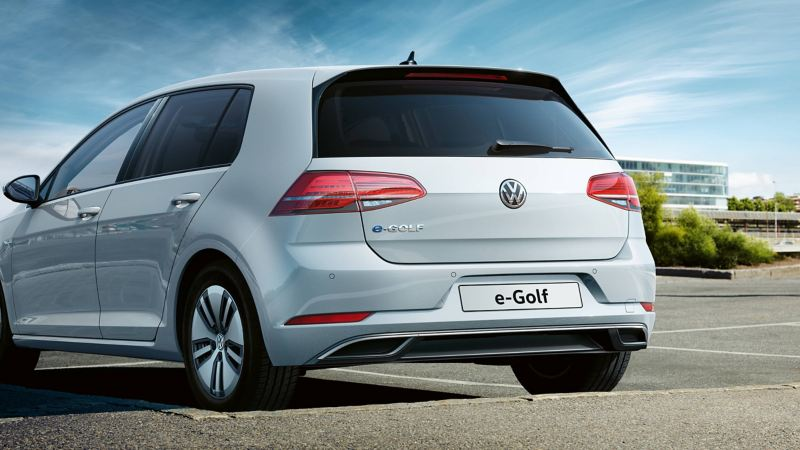A white Volkswagen e-Golf electric vehicle from rear view parked in front of office buildings