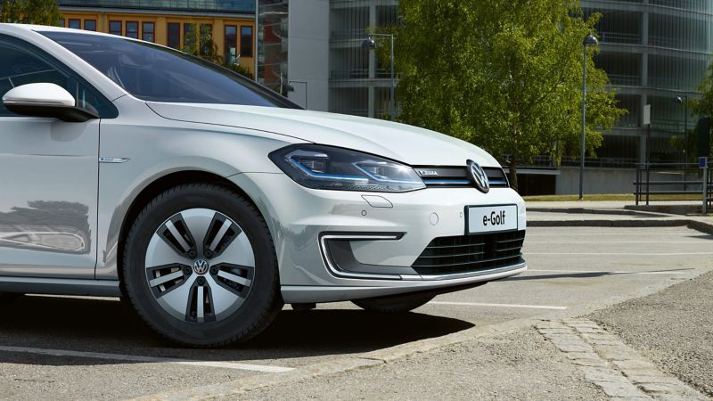The front of a white Volkswagen e-Golf electric vehicle, in a tree-lined office carpark.
