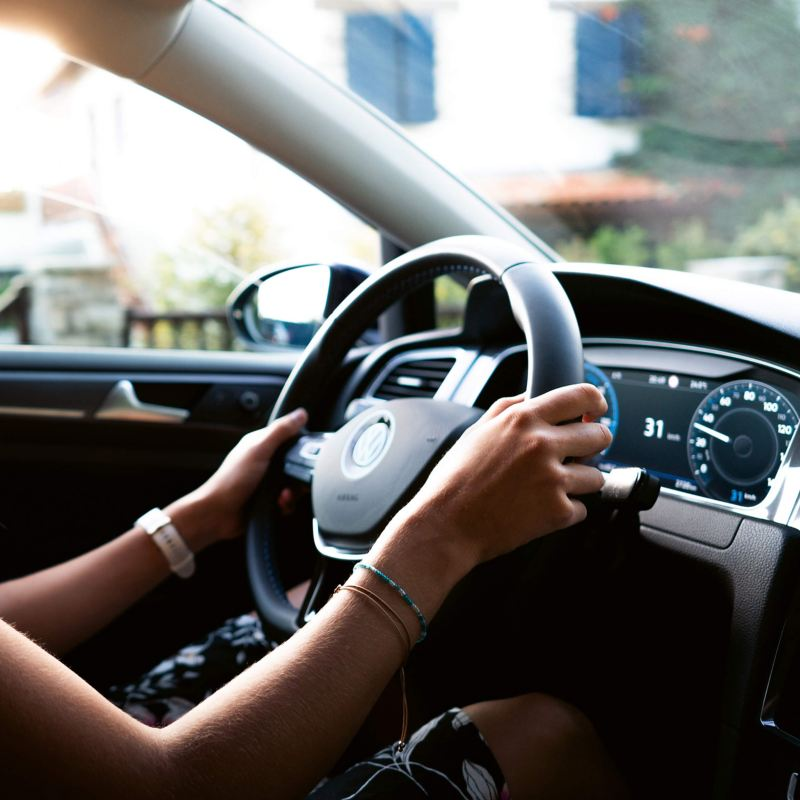 A lady driving a Volkswagen e-Golf.