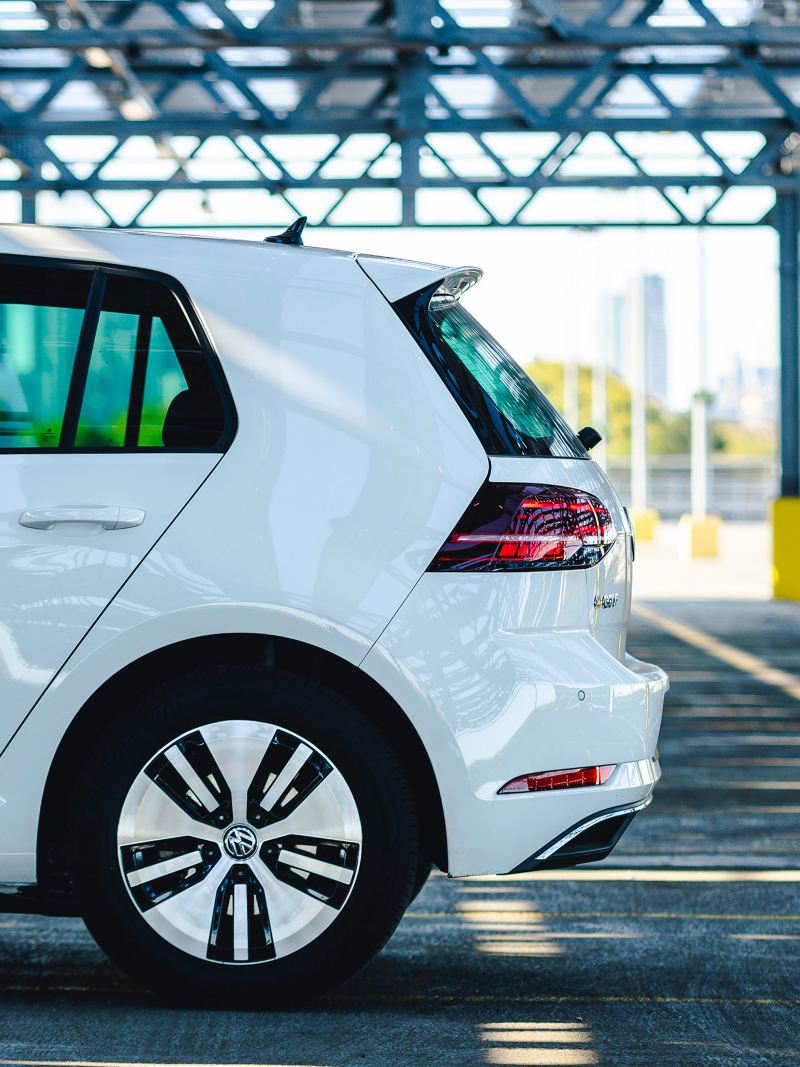 Profile shot of the rear side of a white Volkswagen e-Golf.