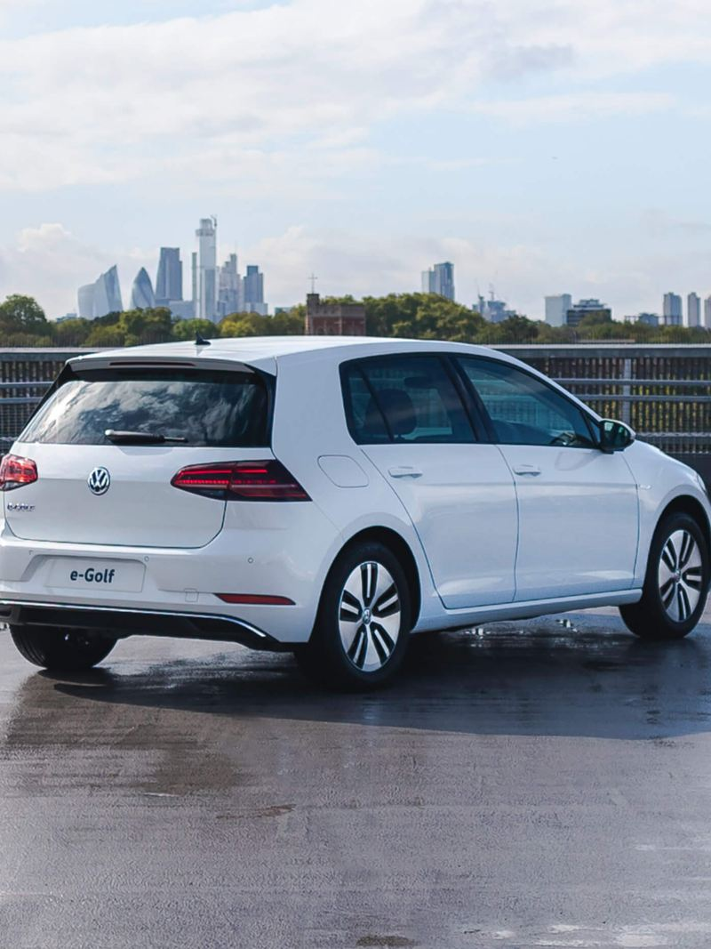 3/4 rear shot of a white Volkswagen e-Golf, parked in the city.