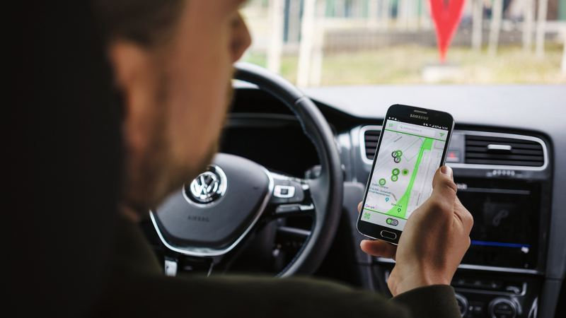 A person inside their Volkswagen, using a charing point locator on their phone.