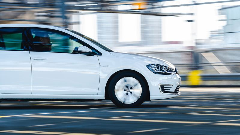 A white Volkswagen e-Golf electric vehicle in motion.