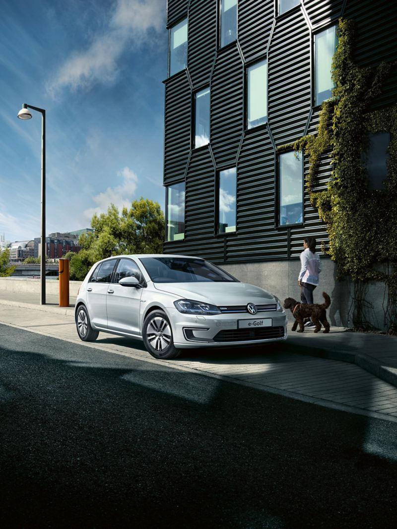 A white Volkswagen e-Golf driving across a bridge.