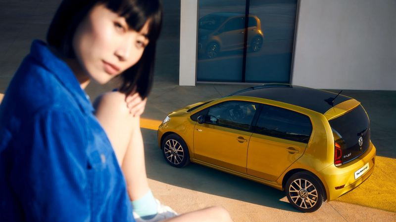 A lady sitting in front of a yellow new e-up!