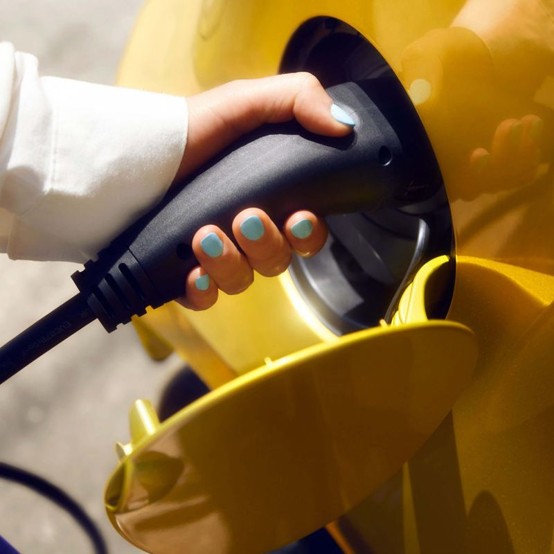 A lady charging her new yellow e-up!