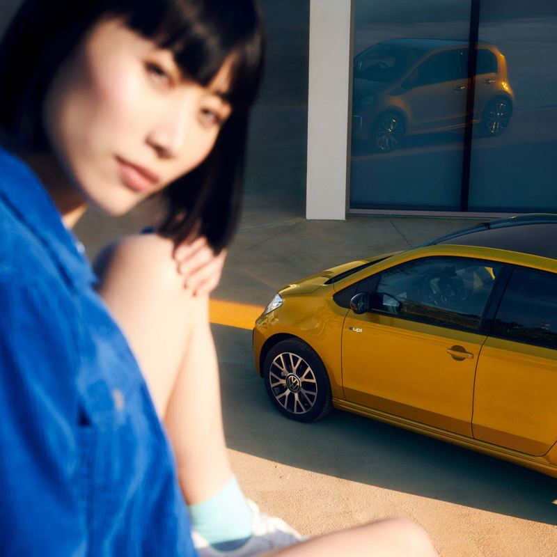 A lady sitting with a yellow new e-up! in the background