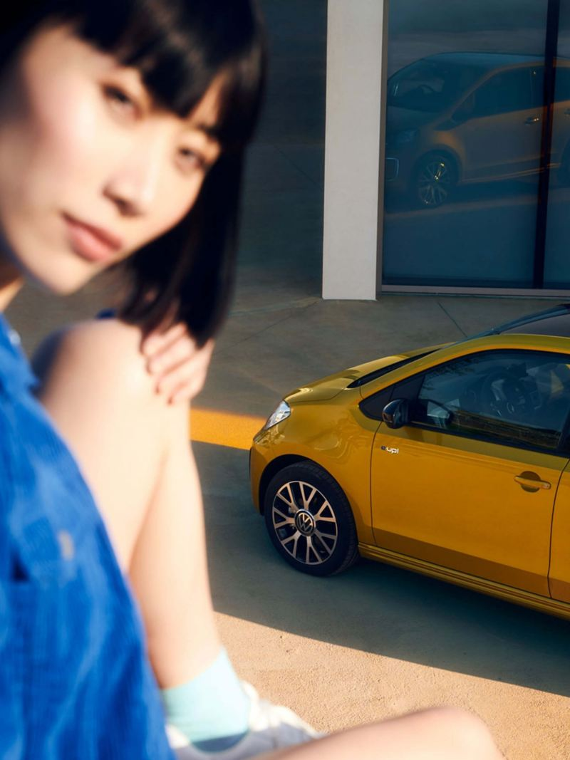 A woman in the foreground with a Volkswagen e-up! in the background
