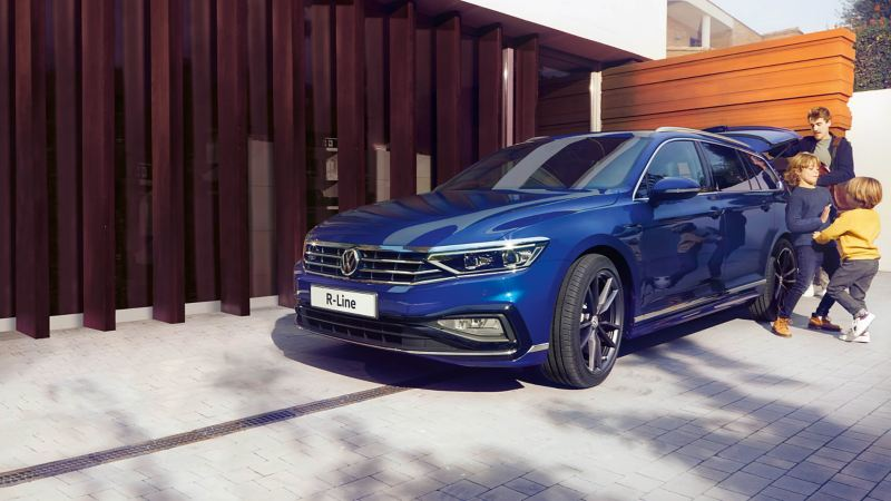 A blue Volkswagen R-Line parked outside family home with children playing while their father is unloading the boot.
