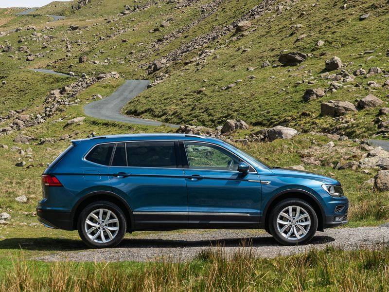 A Green Volkswagen Tiguan Allspace pulled over on the side of a rocky mountain.