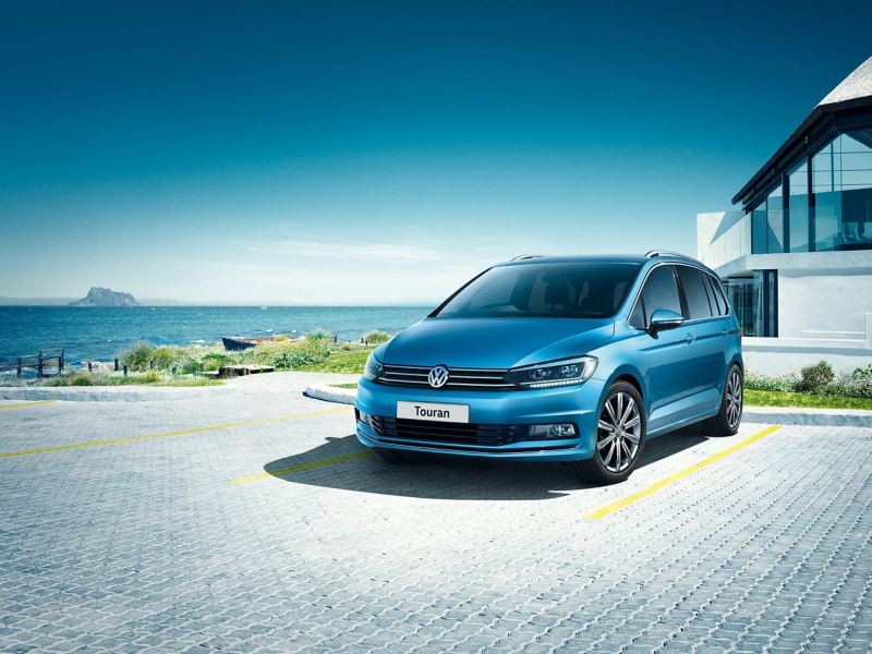 A blue Volkswagen Touran outside a beachfront house, the sea in the background.