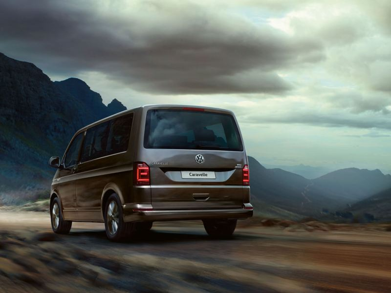 A Volkswagen van for families, the Caravelle driving away into the mountains on an overcast day.