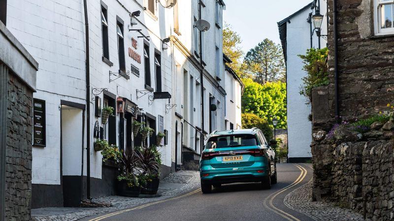 A green Volkswagen Passat Estate, ascending up a narrow village road.