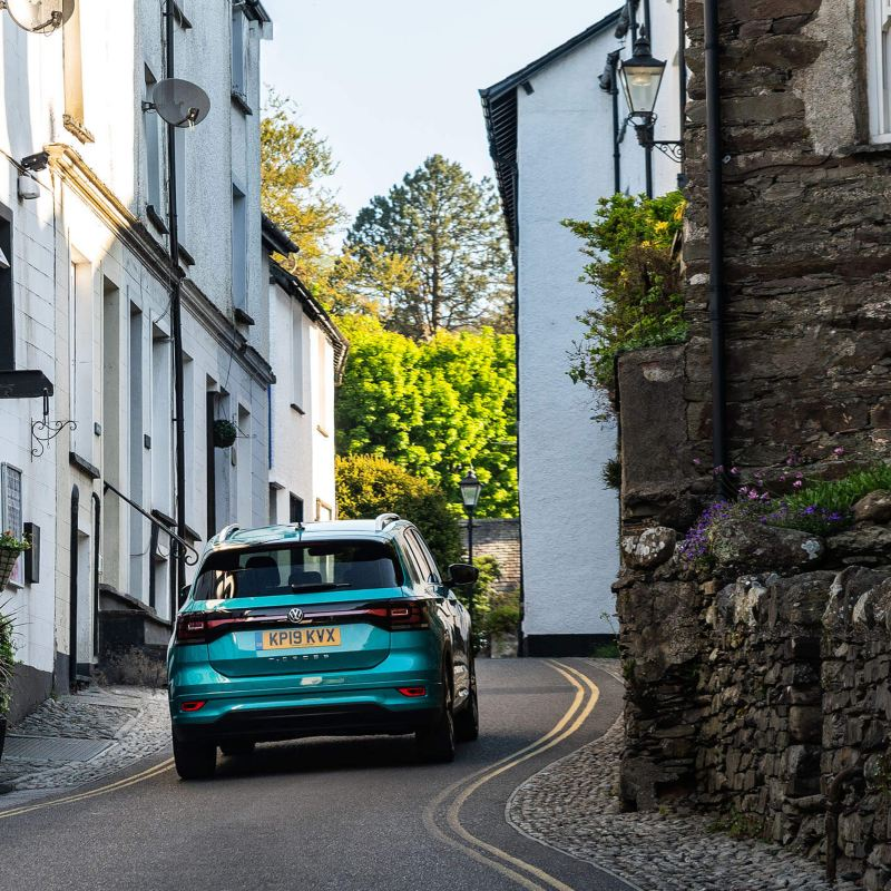 A teal Volkswagen T-Cross, ascending up a narrow village road.