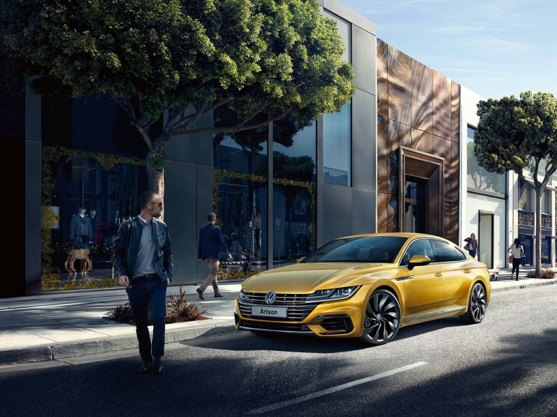 A mustard yellow Volkswagen Arteon parked in a busy tree-lined city street.
