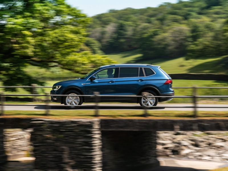 Volkswagen Tiguan Allspace driving over a bridge.