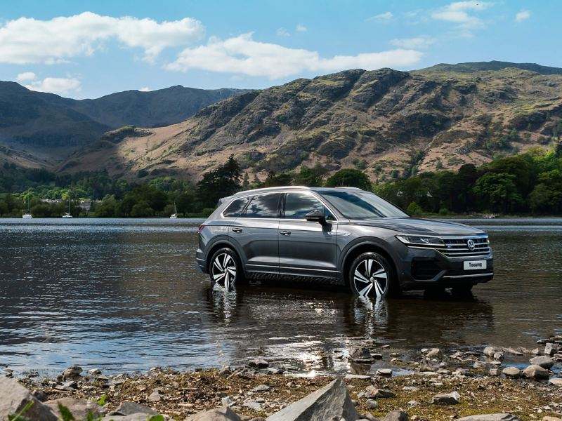 A slate silver Volkswagen Touareg wading through a shallow lake, surrounded by mountains.