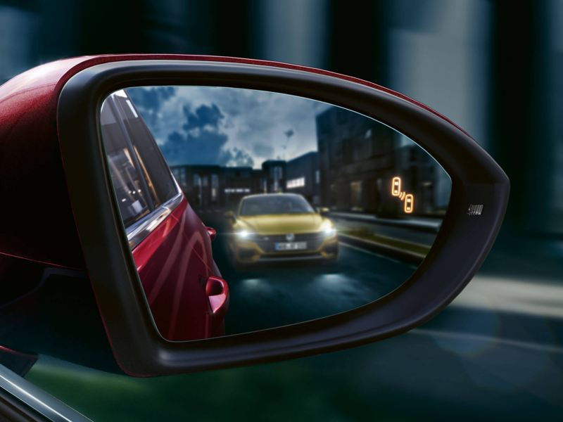 Wing mirror shot of a yellow Volkswagen Arteon at night.