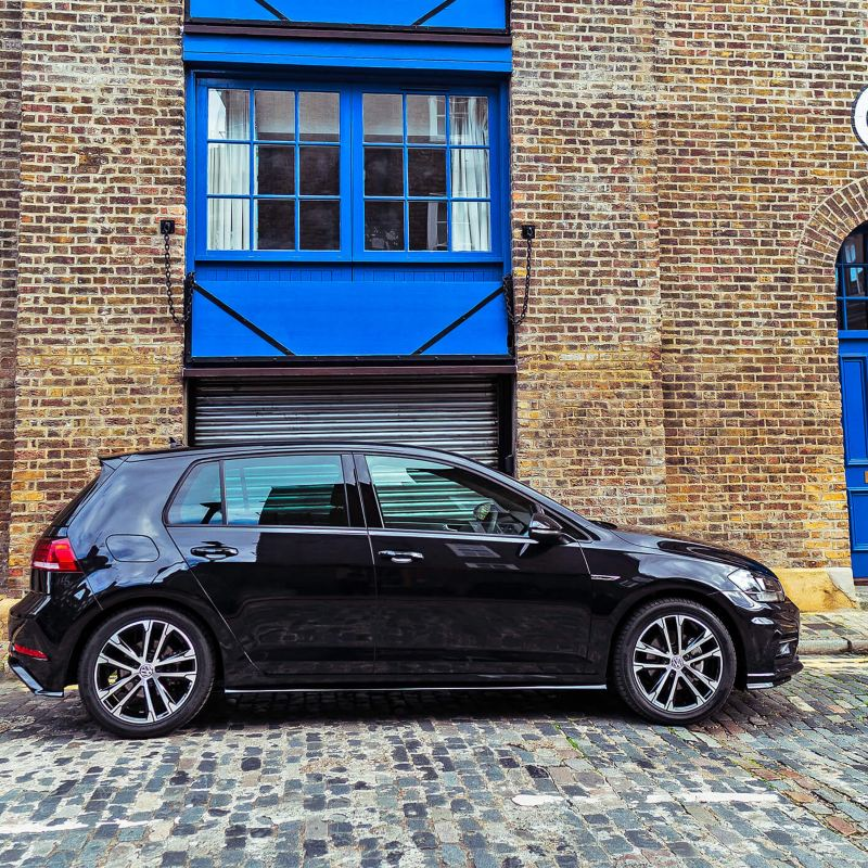 A black Volkswagen Golf next outside a family home.
